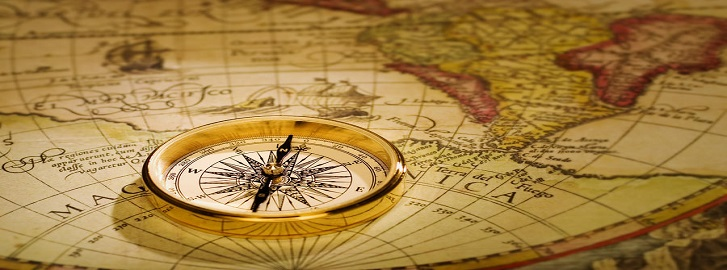 Gold compass laying on world map