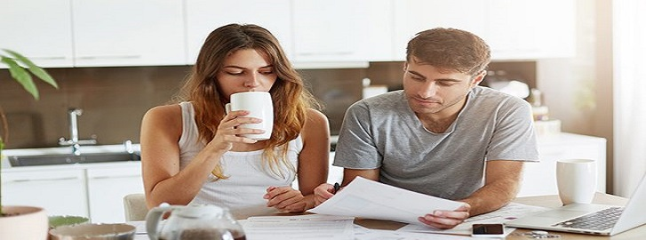 Couple sitting at table reviewing bills