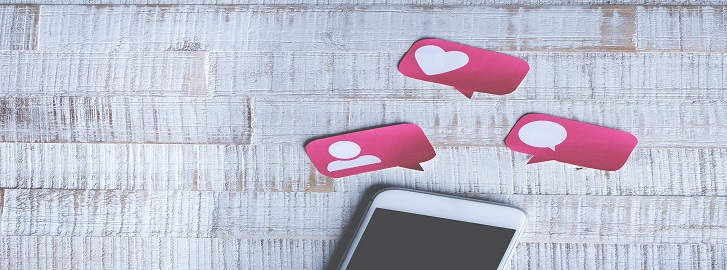 Phone on white table with 3 pink bubbles of a heart, message, and person on them.