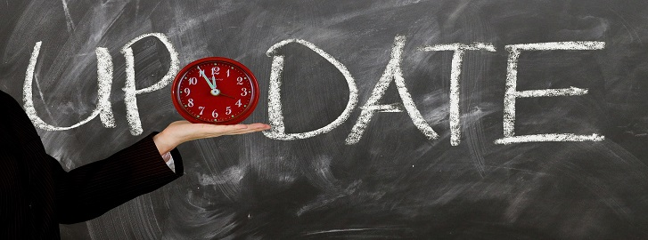 The word Update on a chalkboard with a red clock between up and date