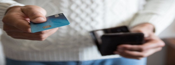 Person holding credit card and wallet